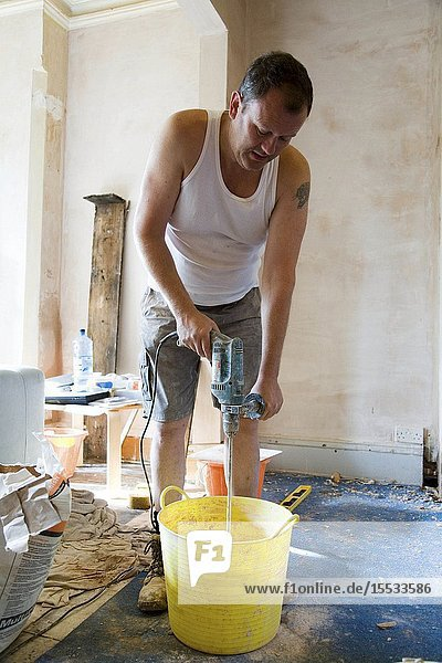 Man using mixing tool to stir plaster in a bucket