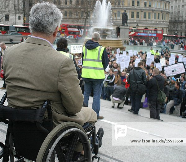 Disabled man at demo in Trafalgar Square London UK.