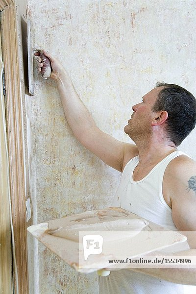 Man using a hawk and trowel to plaster a wall