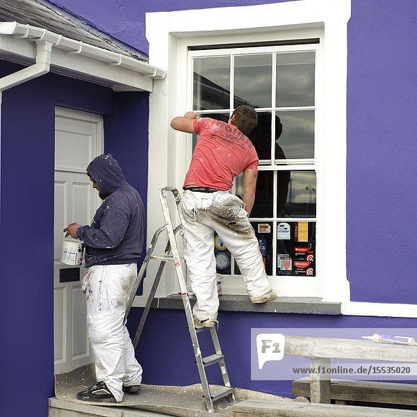Decorators painting house exterior