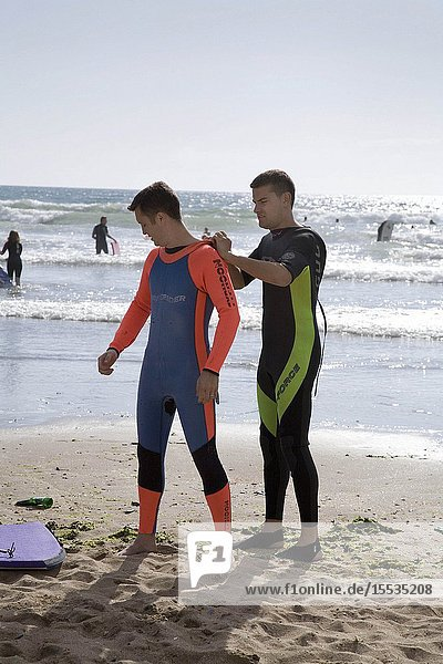 Surfers putting on wetsuits on the beach