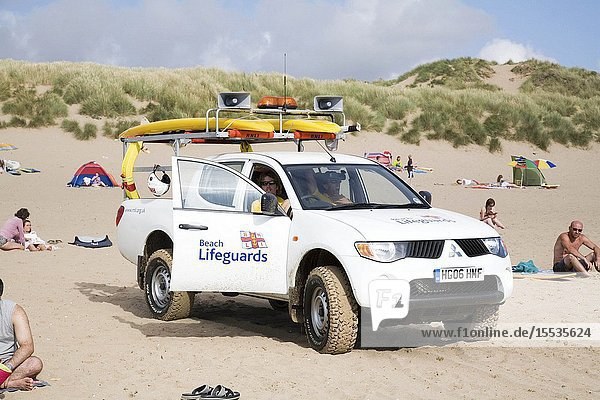 RNLI Lifeguard in his vehicle on the beach