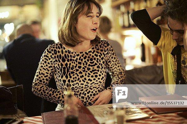 Woman inside restaurant talking to companion
