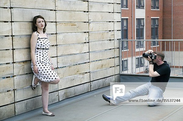 Woman modelling for a photo shoot on a roof top with a photographer