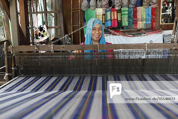Traditional hand loom. Local muslim woman diligently weaving colourful scarves. Chau Doc. Vietnam.
