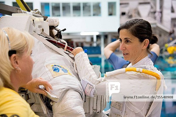NASA astronaut Nicole Stott prepares for a spacewalk training session in the waters of the Neutral Buoyancy Laboratory (NBL) near NASA's Johnson Space Center. Stott is wearing a liquid cooling and ventilation garment that complements the Extravehicular Mobility Unit (EMU) spacesuit. A crew instructor assisted Stott.