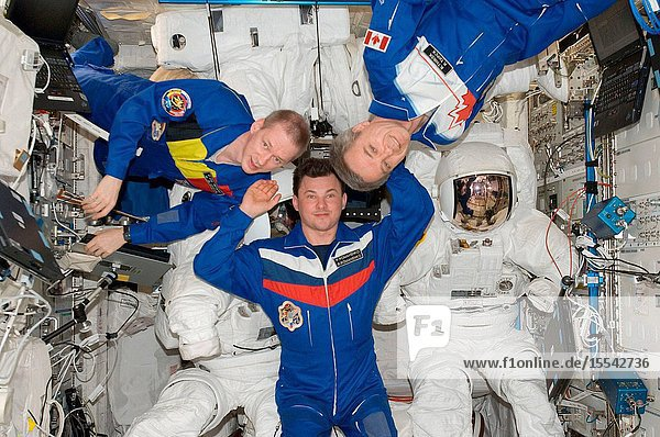 European Space Agency astronaut Frank De Winne (left)  Expedition 21 commander  along with Russian cosmonaut Roman Romanenko (center) and Canadian Space Agency astronaut Robert Thirsk  both flight engineers  pose for a photo with three Extravehicular Mobility Unit (EMU) spacesuits in the Columbus laboratory of the International Space Station.