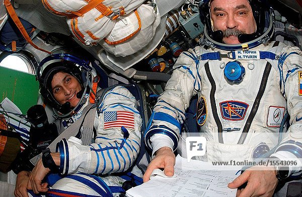 Astronaut Sunita L. Williams (left)  Expedition 14 flight engineer  and cosmonaut Mikhail Tyurin  Soyuz commander and flight engineer  occupy their seats in the Soyuz 13 (TMA-9) spacecraft docked to the International Space Station. Attired in their Russian Sokol launch and entry suits  Tyurin  Williams and astronaut Michael E. Lopez-Alegria (out of frame)  commander and NASA space station science officer  were about to relocate the Soyuz from the Zarya Module nadir port to the Zvezda Service Module aft port in preparation for the arrival of Expedition 15.