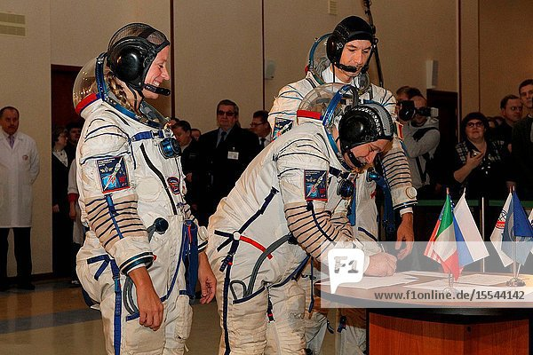 At the Gagarin Cosmonaut Training Center in Star City  Russia  Expedition 34 backup crew members Karen Nyberg of NASA (left) and Luca Parmitano of the European Space Agency (right) look on as Soyuz Commander Fyodor Yurchikhin signs in Nov. 27  2012 at the start of two days of certification exams. The trio was joined by prime crew members Tom Marshburn of NASA  cosmonaut Roman Romanenko and Chris Hadfield of the Canadian Space Agency  who are preparing for launch scheduled for Dec. 19 from the Baikonur Cosmodrome in Kazakhstan in their Soyuz TMA-07M spacecraft for 5 ½  months on the International Space Station.