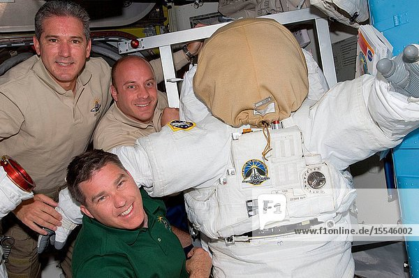 NASA astronauts Michael Good (top)  Garrett Reisman (center) and Steve Bowen  all STS-132 mission specialists  pose for a photo with an Extravehicular Mobility Unit (EMU) spacesuit in the Quest airlock of the International Space Station while space shuttle Atlantis remains docked with the station.