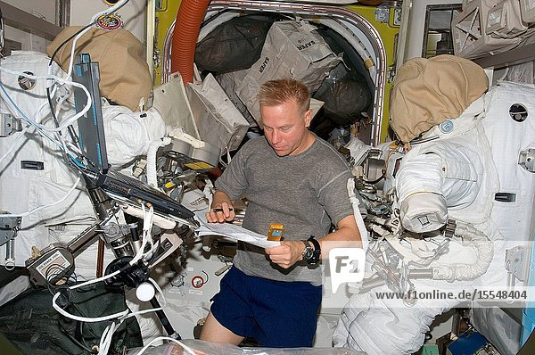 Astronaut Tim Kopra  Expedition 20 flight engineer  looks over a checklist in the Quest airlock of the International Space Station.