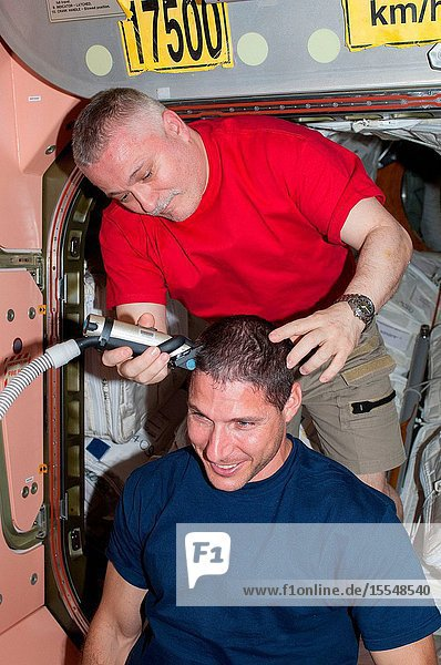 Russian cosmonaut Fyodor Yurchikhin  Expedition 37 commander  trims the hair of NASA astronaut Michael Hopkins  flight engineer  in the Unity node of the International Space Station. Yurchikhin used hair clippers fashioned with a vacuum device to garner freshly cut hair.