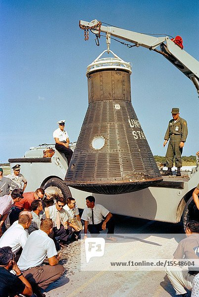 Department of Defense (DOD) recovery personnel and spacecraft technicians from NASA and McDonnell Aircraft Corp.  inspect astronaut John Glenn's Mercury spacecraft  Friendship 7  following its return to Cape Canaveral after recovery in the Atlantic Ocean.
