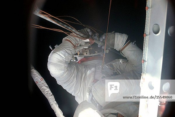 Close-up view of Skylab 2 crew member Joseph P. Kerwin clearing away the remnants (cables and tubing) from the missing solar array panel during an early mission tethered extravehicular activity (EVA) to repair the damaged and partially deployed solar array panel. Conrad's life support umbilical is seen cutting diagonally across the image next to Kerwin. After the successful EVA  the solar panel was fully deployed.