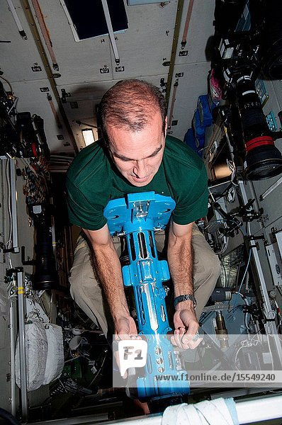 NASA astronaut Rick Mastracchio  Expedition 38 flight engineer  uses a body mass measurement device (BMMD) in the Zvezda Service Module of the International Space Station.