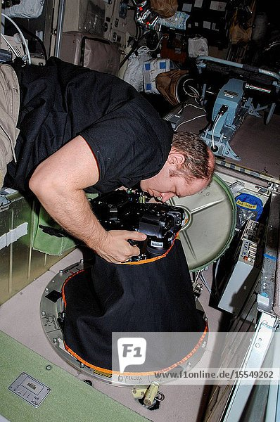 At a window in the International Space Station's Zvezda Service Module  Russian cosmonaut Oleg Kotov  Expedition 38 commander  uses a digital camera photospectral system during a session for the Seiner ocean photography experiment.
