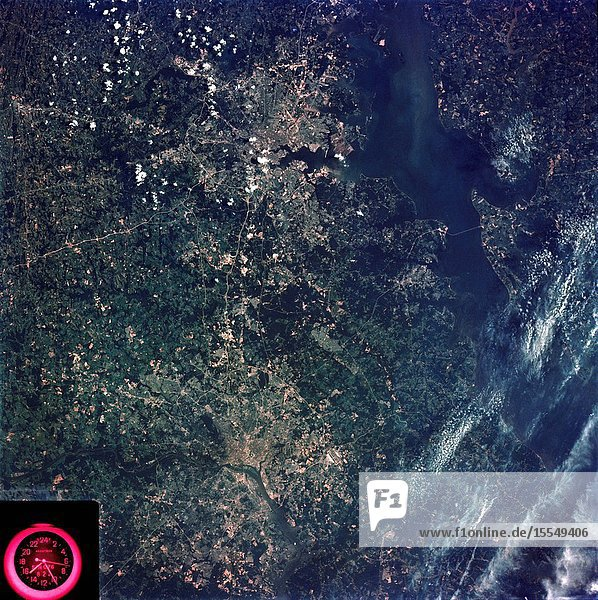 A vertical view of the Washington D.C. and the Baltimore  Maryland area is seen in the Skylab 3 Earth Resources Experiments Package S190-B (five-inch Earth terrain camera) photograph taken from the Skylab space station in Earth orbit. The Chesapeake Bay is on the right (east) side of the picture. The Potomac River flows through the Washington area in the lower left (southwest) corner of the photograph. Several transportation routes and major highways stand out very distinctly. Especially conspicuous are the beltways around the cities  Interstate 95 between Baltimore and the nation's capitol and Interstate 70N leading west from Baltimore. The tunnel and harbor facilities in Baltimore show clearly  also. Identifiable features in the Washington area include the Capitol Building  the Mall area  Robert F. Kennedy Stadium (white circle)  the five bridges across the Potomac  Andrews Air Force Base (on east loop)  and the smaller Anacostia River. The extent of the urbanization in this area is dramatically illustrated in this picture. The photograph has sufficient resolution that the housing patterns for individual suburban areas are clearly defined with the houses shown as pink gray  wooded areas as dark green and cleared areas light green. Chesapeake Bay circulation patterns are indicated by contrast of dark and light blue. Sediment plumes (red) are seen entering the bay north and east of Baltimore. The bay bridge stands out white against the blue water. The detailed information contained in this one photograph will be of direct use to several EREP investigator teams in land use analysis  sedimentation and circulation patterns in the bay  and resource surveys of Maryland. All EREP photography is available to the public through the Department of Interior's Earth Resources Observations Systems Data Center  Sioux Falls  South Dakota  57198.