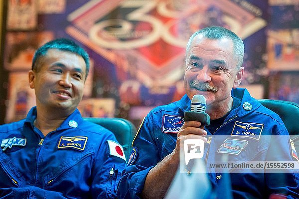 Expedition 38 Soyuz Commander Mikhail Tyurin of Roscosmos  right  talks as Flight Engineer Koichi Wakata of the Japan Aerospace Exploration Agency  listens  from quarantine behind glass  during the final press conference held a day ahead of their launch with fellow crew mate  Flight Engineer Rick Mastracchio of NASA  to the International Space Station  Nov. 6  2013 at the Cosmonaut Hotel in Baikonur  Kazakhstan.