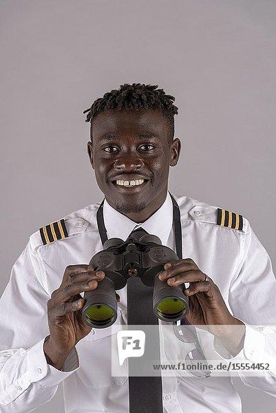 London UK  April 2019. Young airline pilot using a pair of binoculars.