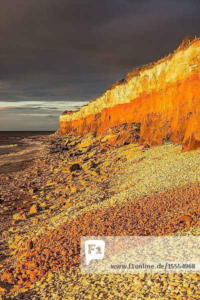 Hunstanton Cliffs at sunset with dark stormy sky  on Norfolk coast  where white chalk overlays red limestone in a colourful formation. England  UK.