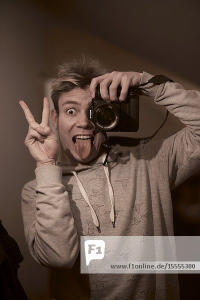 Funny young man taking selfie photograph with professional camera,  throught mirror