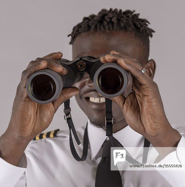 London UK  April 2019. Young airline pilot using a pair of binoculars with focus on hands and lenses.