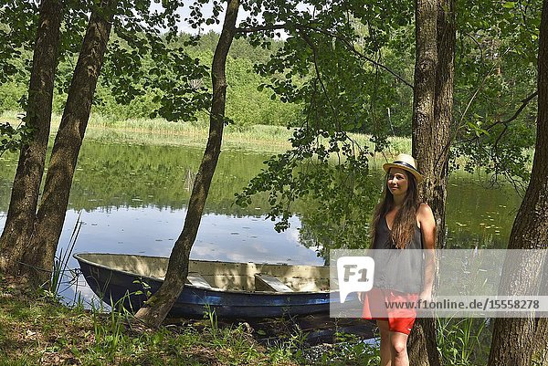Young woman by a lake near Paluse  Aukstaitija National Park  Lithuania  Europe.
