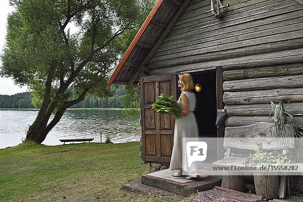 Woman carrying lime branches for the traditional sauna on the edge of Lusiai Lake at Paluse  Aukstaitija National Park  Lithuania  Europe.