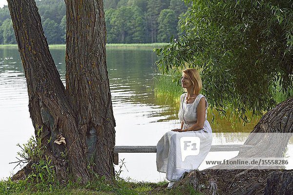 Woman sitting on a bench on the edge of Lusiai Lake at Paluse  Aukstaitija National Park  Lithuania  Europe.