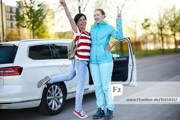 Two adventurous women in front of car with open door  ready to start adventure  in Munich  Germany