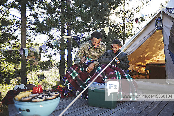 Father and son playing cards outside yurt at campsite