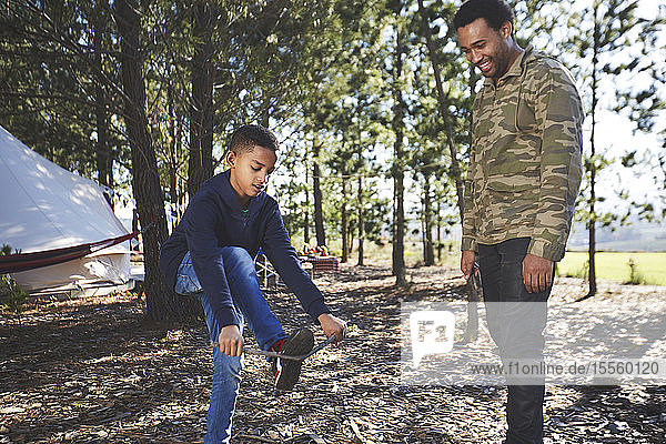 Father watching son breaking kindling at campsite in woods