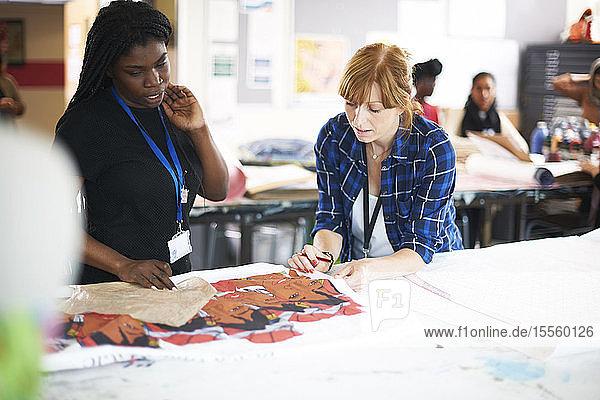 Female artists looking at screen print in art studio