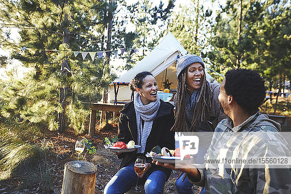 Happy friends laughing and eating at campsite in woods