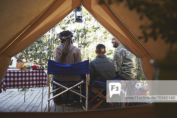Family relaxing outside camping yurt