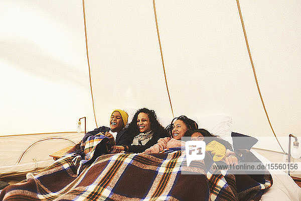 Happy lesbian couple and kids relaxing under blanket in bed in camping yurt