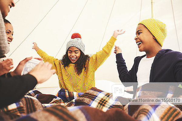 Happy family playing cards in camping yurt