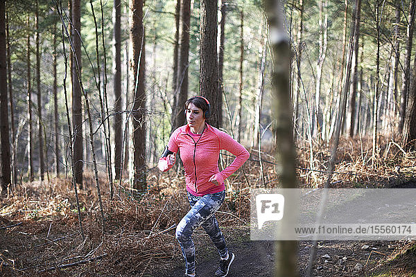 Woman running on trail in autumn woods