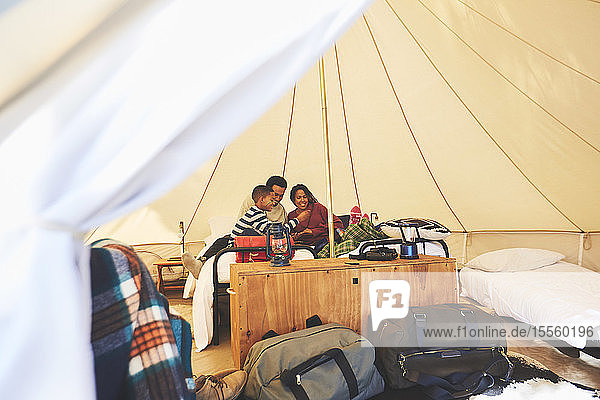 Family relaxing on bed inside camping yurt