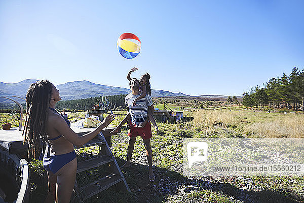 Happy  playful family with beach ball in sunny  summer field