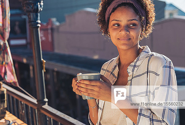 Smiling young woman drinking coffee on sunny balcony