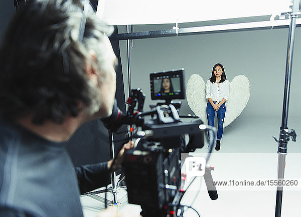 Photographer behind camera photographing young woman wearing angel wings during photo shoot in studio