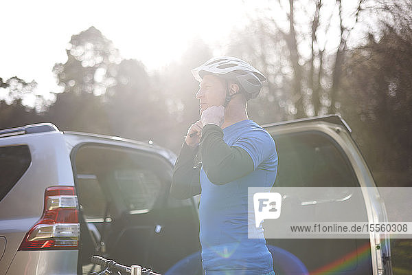 Male cyclist fastening helmet at back of SUV in sunny parking lot