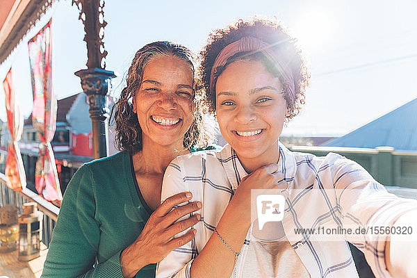 Selfie portrait point of view smiling  happy mother and daughter on sunny balcony