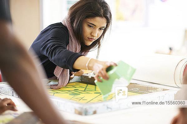Female artist screen printing in art studio