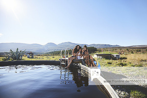 Happy lesbian couple and kids at remote  sunny  summer poolside