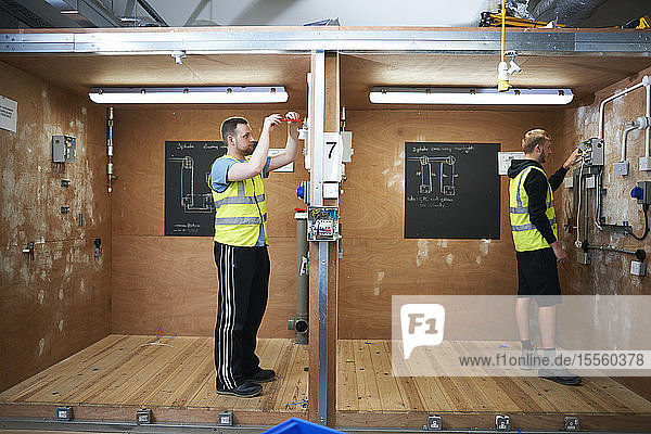 Male electrician students practicing in workshop