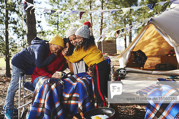 Happy  affectionate lesbian couple and kids hugging at campsite