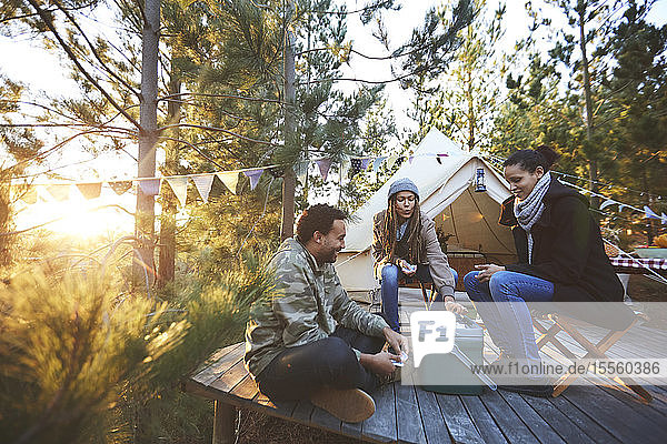 Friends playing cards outside yurt at sunny campsite in woods