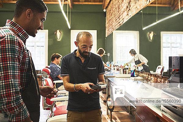 Male customer paying barber in barbershop
